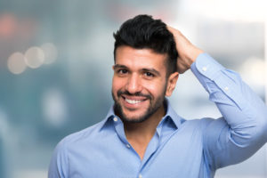 Portrait of a man touching his hair after a succesful hair transplant