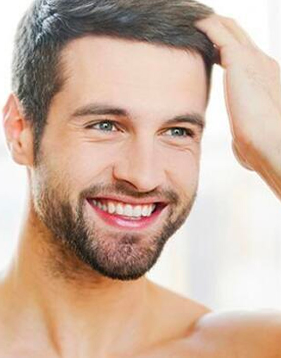 A man smiling after a succesful hair transplant